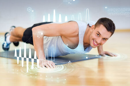 fitness, sport, training, gym and lifestyle concept - smiling man doing push-ups in the gym photo