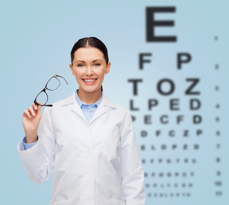 healthcare, vision and medicine concept - smiling female doctor with glasses and eye chart photo