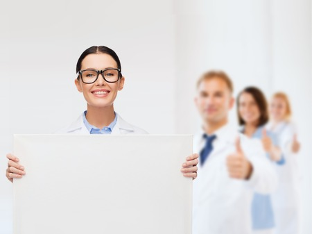 healthcare, advertisement and medicine concept - smiling female doctor in eyeglasses with white blank board photo