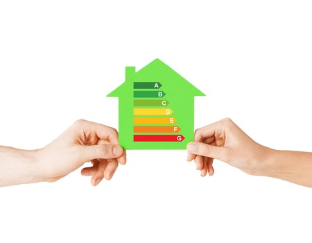 energy saving, real estate and family home concept - closeup of couple hands holding green paper house with energy efficiency rating photo