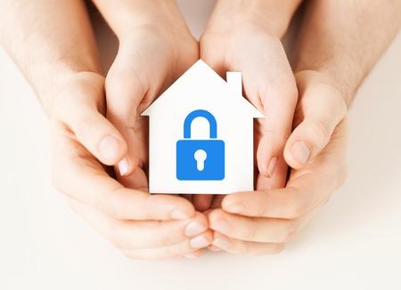 onroerende goederen en het concept van de familiehuisveiligheid - close-upbeeld van mannelijke en vrouwelijke handen die Witboekhuis met blauw slot houden