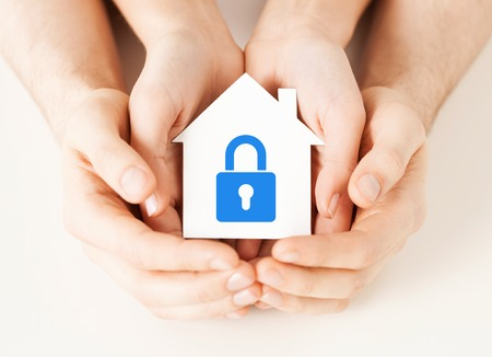 real estate and family home security concept - closeup picture of male and female hands holding white paper house with blue lock