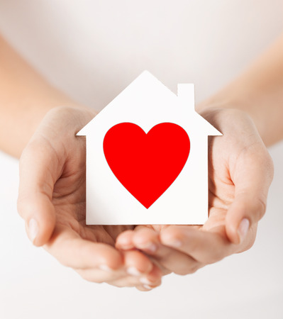 house in hand: charity, real estate and family home concept - closeup picture of female hands holding white paper house with red heart