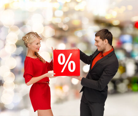 shopping, sale, christmas, couple and mall concept - smiling woman and man with red percent sale sign at shopping mall photo