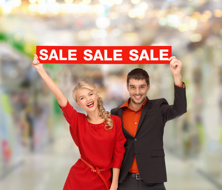 shopping, sale, christmas, couple and mall concept - smiling woman and man with red sale sign at shopping mall photo