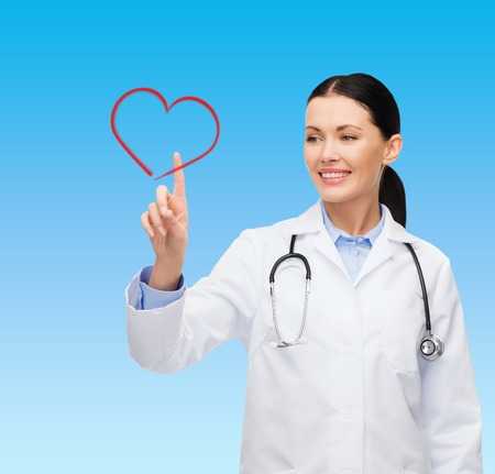 healthcare, medicine and technology concept - smiling female doctor pointing to heart