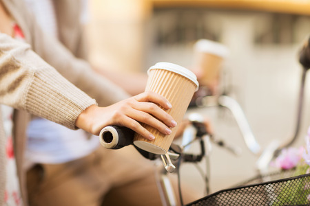 bicycle girl: summer holidays, bikes, love, relationship and dating concept - closeup of woman hand holding coffee and riding bicycle