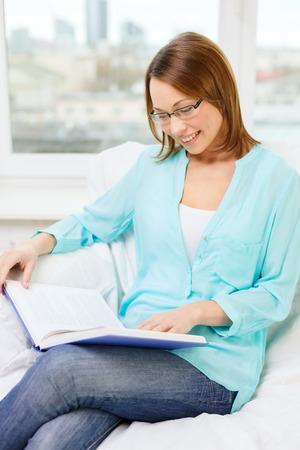 leasure and home concept - smiling woman in eyeglasses reading book and sitting on couch at home Stock Photo - 25626161