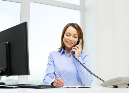 making notes: business, communication and education concept - smiling businesswoman with laptop, documents and telephone