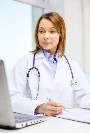 taking notes: medicine and healthcare concept - busy doctor with laptop computer