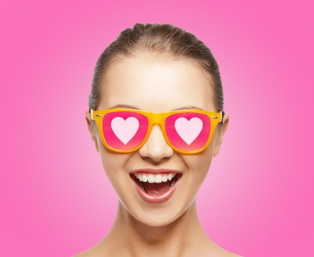 love, happiness and valentines day concept - amazed teen girl in sunglasses with hearts on pink background photo