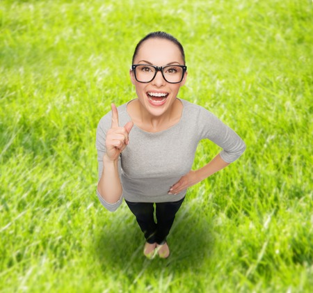 people looking up: happiness and gesture concept - smiling asian woman in eyeglasses with finger up