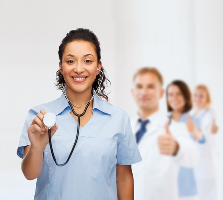 healthcare and medicine concept - smiling female african american doctor or nurse with stethoscope photo
