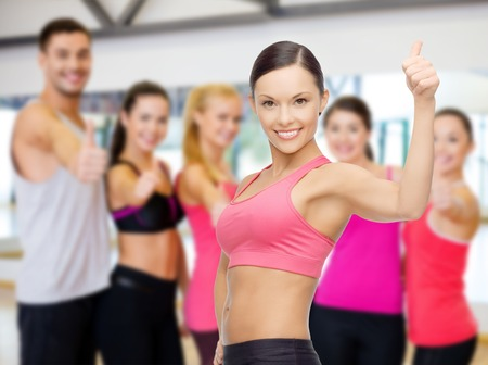 pumping: fitness, sport, training and lifestyle concept - personal trainer with group of smiling people in gym