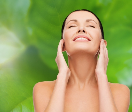 health, spa and beauty concept - clean face and hands of beautiful smiling woman with closed eyes photo