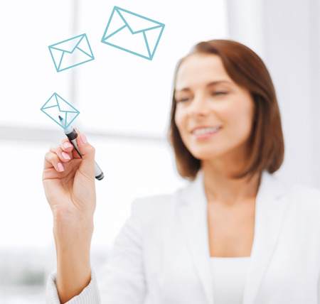 office, business, technology concept - businesswoman drawing envelopes in the air with marker photo