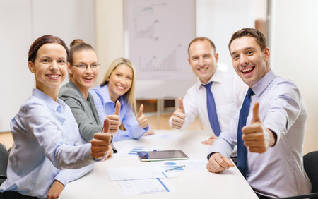 business, success, technology and office concept - smiling business team with tablet pc computer and papers showing thumbs up in office Stock Photo