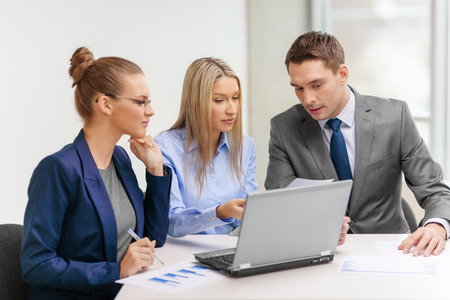 business results: business, technology and office concept - concentrated business team with laptop computers and documents having discussion in office