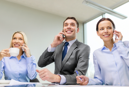 business, technology and office concept - smiling business team with smartphones making calls in office photo