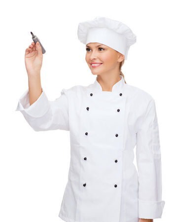 cooking, new techology , advertisement and food concept - smiling female chef, cook or baker with marker writing something on virtual screen photo