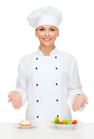 asian cook: cooking and food concept - smiling female chef, cook or baker with salad and cake on plates