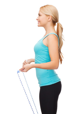 sport, excercise and healthcare - sporty woman with skipping rope photo
