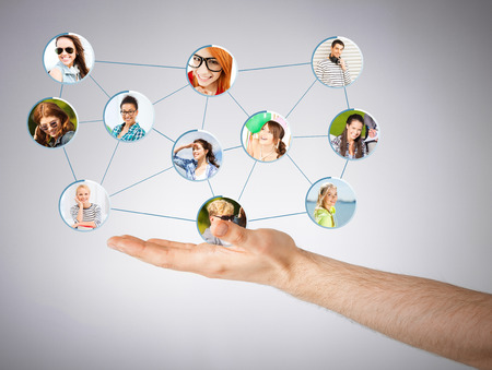 networking and communication concept - closeup of mans hand showing social network photo
