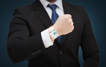 time, business and new technology concept - close up of businessman showing something at his hand photo