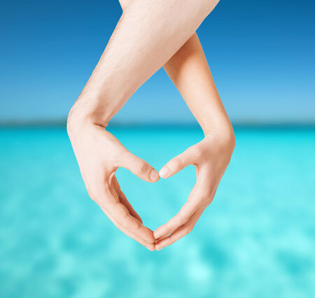 love, summer holidays and vacation concept - close up of woman and man hands showing heart shape photo