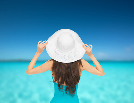 vacation and summer holidays concept - model in swimsuit with hat photo