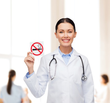 oncologist: healthcare and medicine concept - smiling female doctor with stethoscope holding no smoking sign Stock Photo
