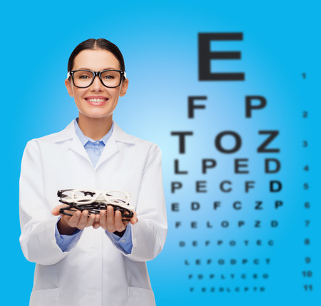 healthcare, vision and medicine concept - smiling female doctor with many eyeglasses and eye chart photo