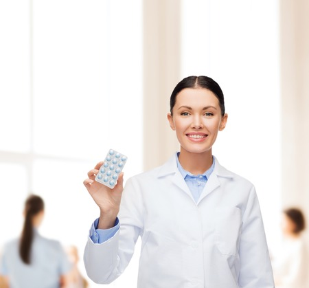 aspirin: healthcare, medicine and pharmacy concept - smiling female doctor and with pills