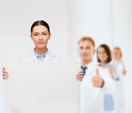 thumbs up group: healthcare, advertisement and medicine concept - calm female doctor with white blank board Stock Photo