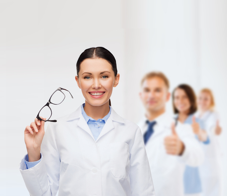 healthcare, vision and medicine concept - smiling female doctor with eyeglasses photo