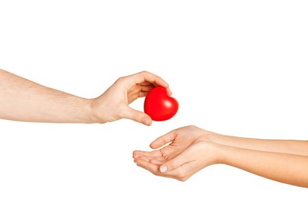 love, relationship, charity and medicine concept - man hand giving red heart to woman photo