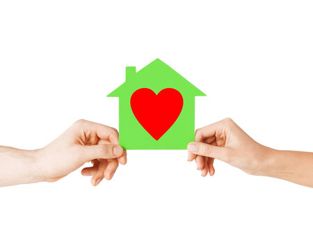 charity, real estate and family home concept - isolated picture of male and female hands holding green paper house with red heart photo