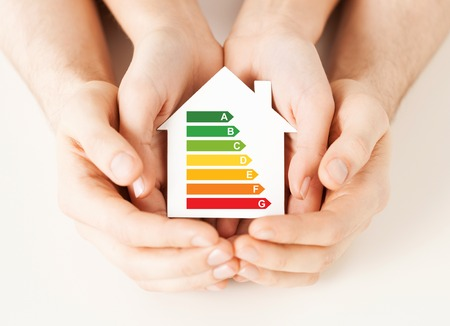 energy saving, real estate and family home concept - closeup of couple hands holding white paper house with energy efficiency rating Stock Photo