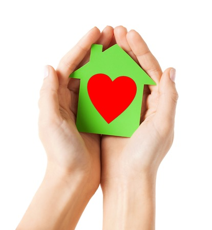 charity, real estate and family home concept - closeup picture of female hands holding green paper house with red heart photo