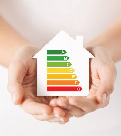 ahorro energetico: ahorro de energía, los bienes raíces y el concepto de hogar - primer plano de las manos femeninas que sostienen la casa de papel blanco con índice de eficiencia energética Foto de archivo