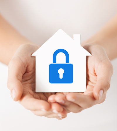 guard house: real estate and family home security concept - closeup picture of female hands holding white paper house with blue lock