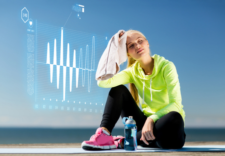 resting heart rate: sport and lifestyle concept - woman resting after doing sports outdoors Stock Photo