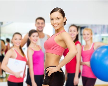 aseo personal: fitness, deporte, entrenamiento y estilo de vida concepto - entrenador personal con un grupo de gente sonriente en el gimnasio