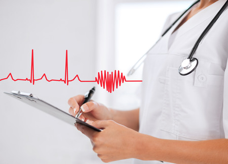 heart disease: healthcare and medical concept - female doctor with stethoscope writing prescription