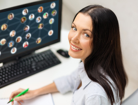 making notes: networking, business and technology concept - smiling businesswoman studying with computer