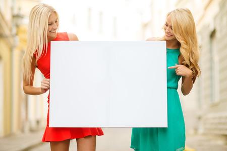 bachelorette party: summer holidays, , travel, tourism and advertisement concept - two happy blonde women with blank white board in the city