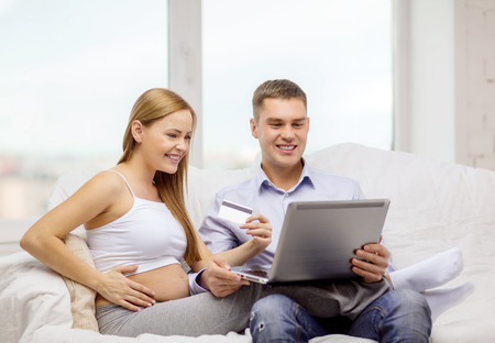 pregnancy, parenthood, internet, banking, money and technology concept - expecting family with laptop computer and credit card photo