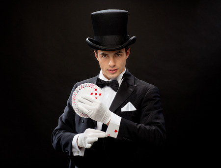 magic show: magic, performance, circus, gambling, casino, poker, show concept - magician in top hat showing trick with playing cards Stock Photo