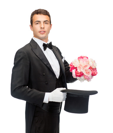 conjuring: magic, performance, circus, show concept - magician taking out of top hat flower bouquet Stock Photo