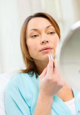 mirror face: cosmetics and beauty concept - beautiful woman applying lipstick and holding mirror Stock Photo
